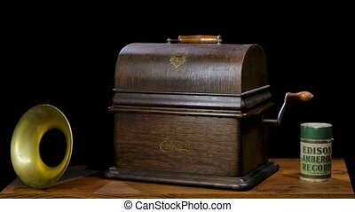 A wooden suitcase with an Edisson phonograph emerges from the darkness. Vintage retro musical instrument on table next to the horn in a dark studio. Historical value. Antiques. Close up. Slow motion