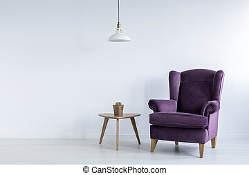 A wooden table and a fancy, dark purple, wing armchair in an empty living room interior with white walls and place for furniture. Real photo.