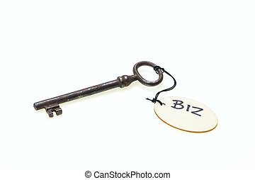 "A wooden tag with ""biz"" text on old rusty key, isolated on white background"