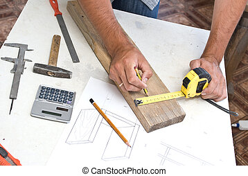 A woodworker measures the mark for his cut