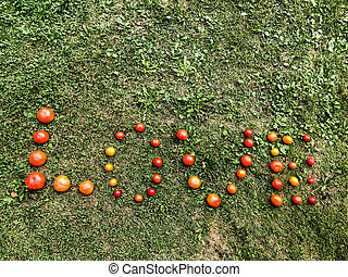 A word from a tomato, letters L, O, V, E. The word LOVE. Letters from red and yellow tomatoes on green grass. Valentine's Day. Creative declaration of love. Love of food, love of food and healthy eating