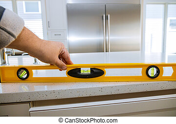 A worker checks the leveling of granite countertops in a home kitchen remodel