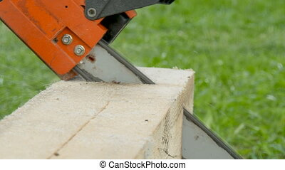 A worker cuts a wooden beam with a gasoline saw