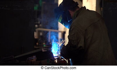 A worker in a uniform uses a welding machine, producing...