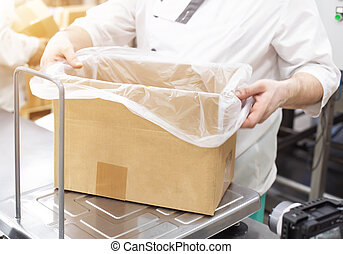 A worker in production weighs products in a box on scales, packing and sorting products by weight, industry