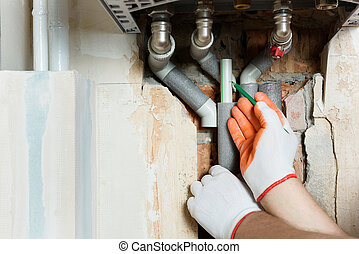 A worker is installing the gas boiler pipes.