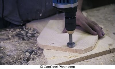 A worker is processing a hole in a wood by using a power hole saw.