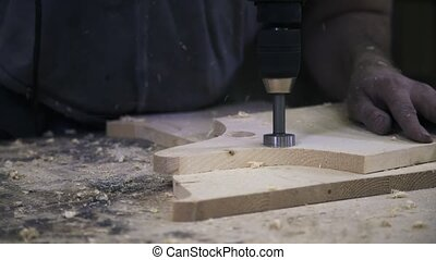 A worker is sawing a wooden bar using a power hole saw.
