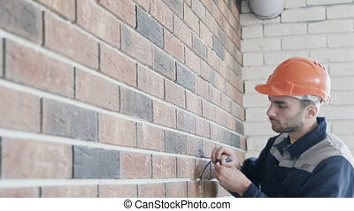 a worker measuring a wall with a tape measure