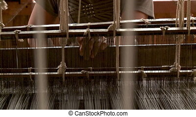 A worker operating the loom machine in the factory
