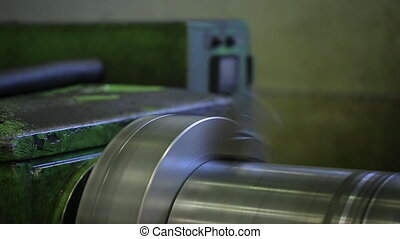 A worker polishes a shiny metallic rotating part on a lathe....