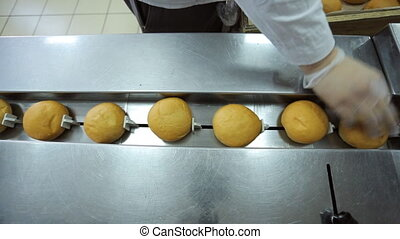 A worker puts freshly baked rolls on conveyor for packaging.