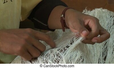 A worker removing fibres on silk thread by hand - A closeup ...