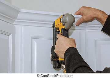 A worker using portable air gun nail in the nailing to crown moldings on new kitchen