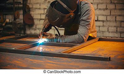 A worker welding the seams between the metal beams