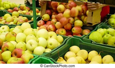 A Working Man In The Supermarket Puts Fruit Apples Trays