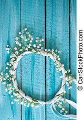 A wreath of lilies of the valley on blue