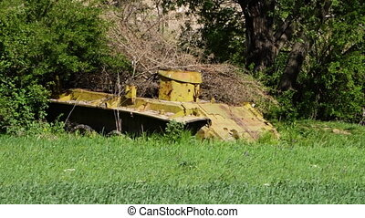 A yellow abandoned tank body - A steady, medium shot of a...