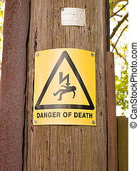a yellow and black danger of death sign with triangle and lightening bolt on a wooden electric pole pylon