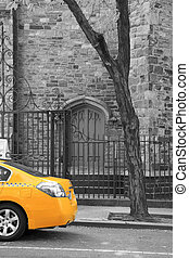 A yellow cab is parking in front of a historic building in black and white