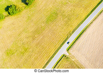 a yellow car on a country road in the summer from above