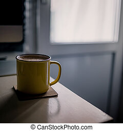 A yellow cup of coffee stands on the office desk in the sunny morning-evening light, next to the monitor and keyboard