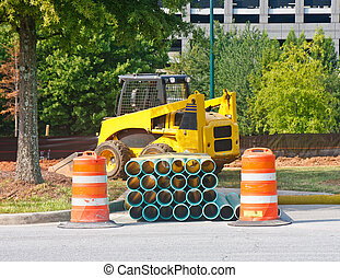 A yellow front end loader behind pipes and orange barrels