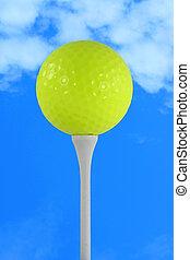 Yellow golf ball against blue sky