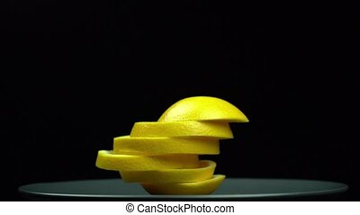 A yellow orange spinning on a plate on a black background is...