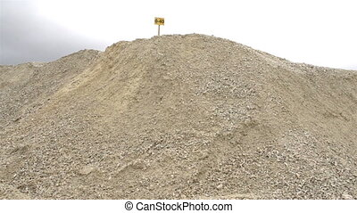 A yellow sign on top of the hill of limestone