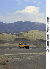 A yellow SUV parking in the desert