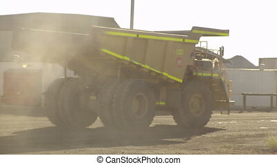 A yellow truck on a dusty road - A full shot of a truck...