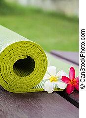 yoga mat - A yoga mat is set on the floor beside flowers