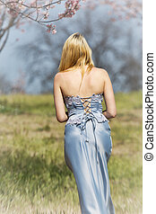 A young 20 something blond woman in a long, blue, dress walks in a grass meadow with her back to the camera. Photograph features a cherry blossom background