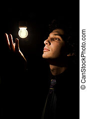 a young actor dressed as a businessman taking a pose in stage lighting