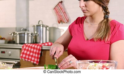 A young adult woman is preparing a vegetable salad sitting ...