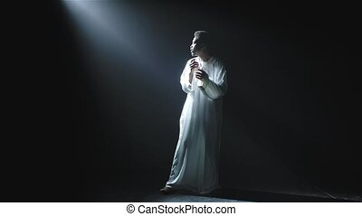 A young African American man in a white hoodie looks at the beam of light in dismay and says wow with a shocked expression on his face. Picture taken in the studio on a black background