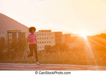a young African American woman jogging outdoors