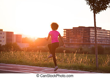 a young African American woman jogging outdoors - young...