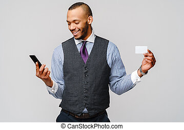 a young African businessman using his smartphone to shop online while holding his credit card