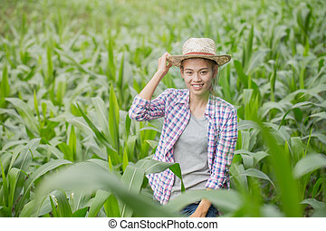A young and beautiful farmer happily smiles in his corn garden.