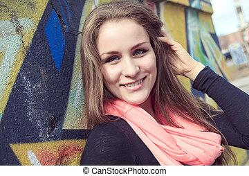 Young and beautiful girl posing against graffiti wall