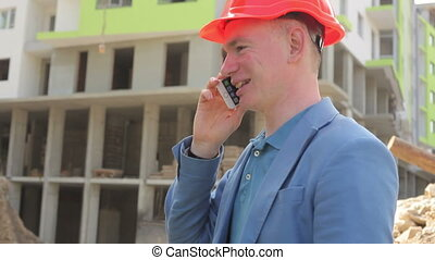 young architect talking on the phone at the construction site