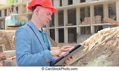 young architect working on a tablet near the construction site