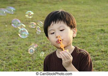 A young Asian boy blowing bubbles at a public park