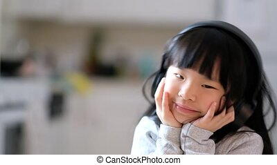 A young asian girl enjoying listening to music on her headphone