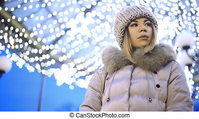 A young Asian girl looks in a park the city at night on the background lights. On both sides Slide