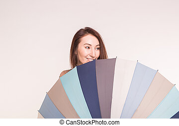 A young asian woman behind colourful umbrella on white background