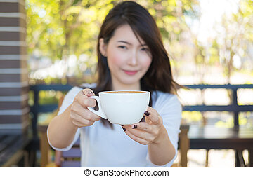 A young Asian woman holding a cup of coffee on hand with happiness