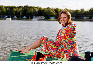 A young athletic girl in robe sits on the pier